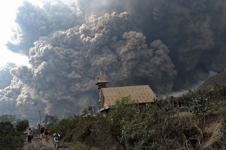 A giant cloud of hot volcanic ash clouds engulfs villages in Karo district during the eruption of Mount Sinabung volcano located in Indonesia's Sumatra island on February 1, 2014. (Sutanta Adiya/AFP/Getty Images)