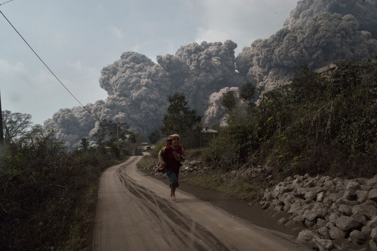 A resident runs away to escape from hot volcanic ash clouds engulfing villages in Karo district during the eruption of Mount Sinabung volcano located in Indonesia's Sumatra island on February 1, 2014. (Sutanta Adiya/AFP/Getty Images)