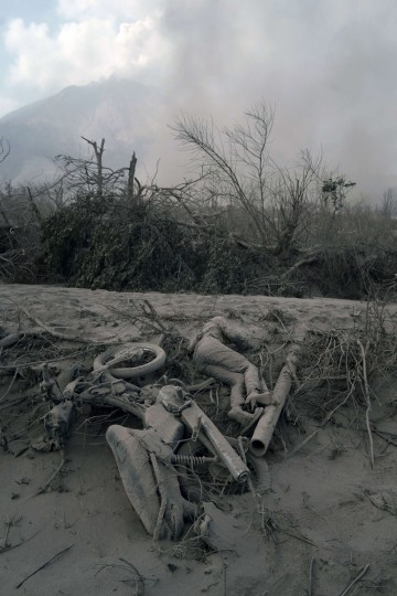 The body of a victim is covered with hot volcanic ash at a village in Karo district following eruptions of Mount Sinabung volcano, seen in the background, located in Indonesia's Sumatra island on February 1, 2014. (Sutanta Adiya/AFP/Getty Images)
