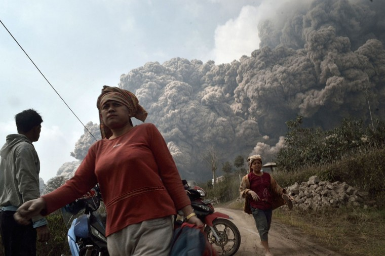 Residents run away to escape from hot volcanic ash clouds engulfing villages in Karo district during the eruption of Mount Sinabung volcano located in Indonesia's Sumatra island on February 1, 2014. (Sutanta Adiya/AFP/Getty Images)