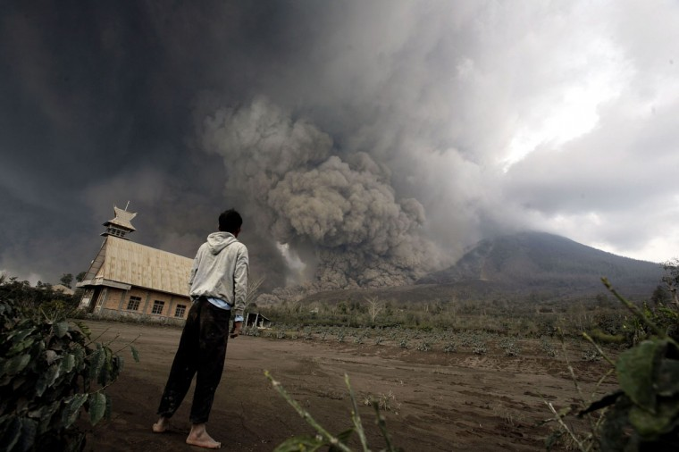 A resident looks at giant volcanic ash clouds from a village in Karo district during the eruption of Mount Sinabung volcano located in Indonesia's Sumatra island on February 1, 2014. (Chaideer Mahyuddin/AFP/Getty Images)