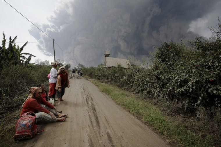 Residents rest after evacuating from villages engulfed by giant volcanic ash clouds in Karo district during the eruption of Mount Sinabung volcano located in Indonesia's Sumatra island on February 1, 2014. (Chaideer Mahyuddin/AFP/Getty Images)