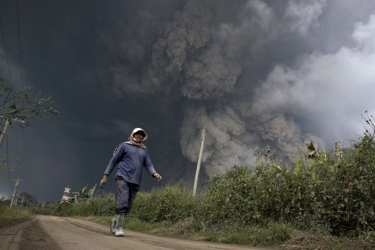 A resident evacuates from hot volcanic ash clouds engulfing villages in Karo district during the eruption of Mount Sinabung volcano located in Indonesia's Sumatra island on February 1, 2014. (Chaideer Mahyuddin/AFP/Getty Images)