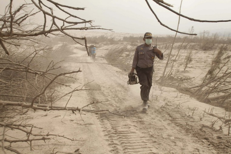 A policeman walks through ash during rescue operations after the Mount Sinabung eruption, near Suka Meriah village in Karo, North Sumatra province February 2, 2014. (Tarmizy Harva/Reuters)