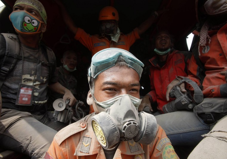 Rescue team members take a break during rescue operations after the Mount Sinabung eruption near Suka Meriah village in Karo, North Sumatra province February 2, 2014. (Yt Haryono/Reuters)
