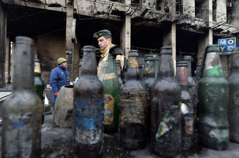 A man walks past empty Molotov cocktail bottles on Kiev's Independence Square on February 22, 2014. (Sergei Supinsky/AFP Getty Images)
