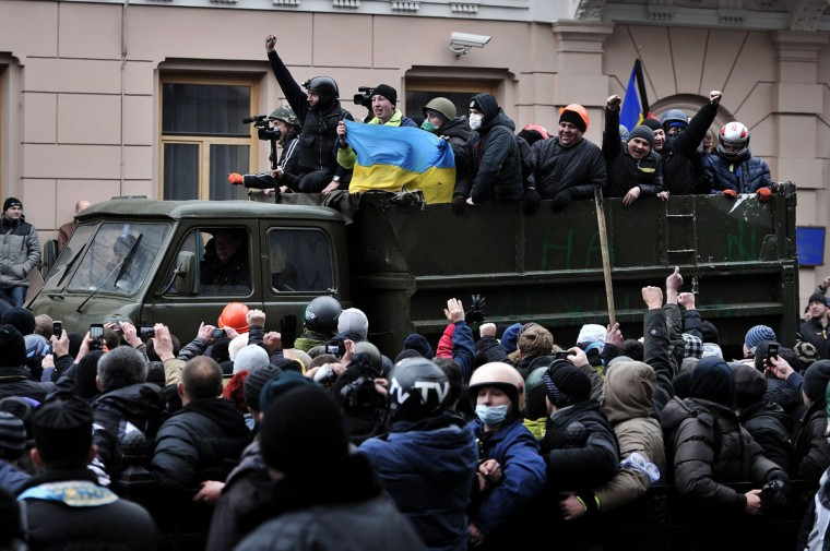 People cheer as anti-government protesters arrive outside the Parliament in Kiev on February 22, 2014. Ukrainian President Viktor Yanukovych said on February 22 he would not sign any of the new laws passed by parliament, which included a measure to release the jailed opposition leader Yulia Tymoshenko. (Louisa Gouliamaki/AFP/Getty Images)
