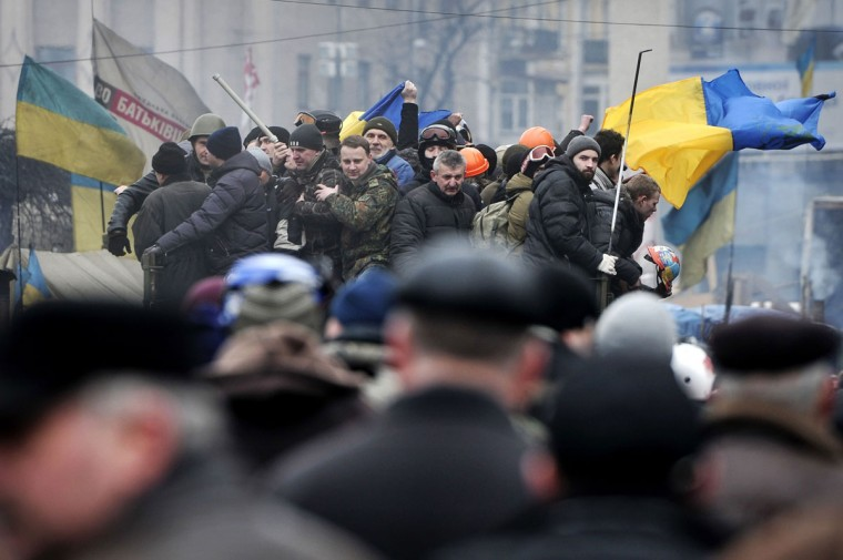 Anti-government protesters ride on a military truck in Kiev on February 22, 2014. Ukrainian President Viktor Yanukovych said on February 22 he would not sign any of the new laws passed by parliament, which included a measure to release the jailed opposition leader Yulia Tymoshenko. (Louisa Gouliamaki/AFP/Getty Images)