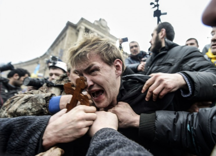 An alleged sniper (center) and member of the pro-government forces is beaten by anti-government protestors in Kiev on February 22, 2014. The regime of Ukraine's president appeared close to collapse on February 22 as the emboldened opposition took control of central Kiev and key government and parliament positions and voted to immediately free its jailed leader Yulia Tymoshenko. (Bulent Kilic/AFP/Getty Images)