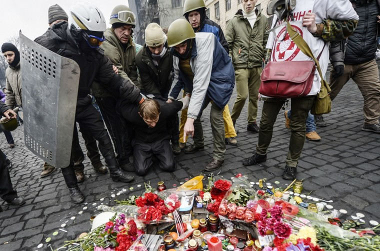 A man (center) suspected of being a sniper and member of the pro-government forces is forced by anti-government protestors to pay his respects to a mourning place of a victim killed in the recent clashes in Kiev on February 22, 2014. (Bulent Kilic/AFP/Getty Images)