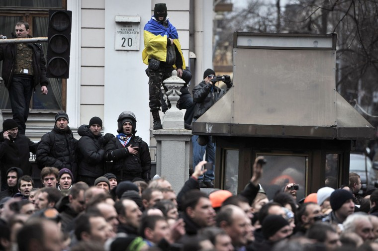 People gather outside the parliament in Kiev on February 22, 2014. A member of Ukraine's parliament said on February 22 that President Viktor Yanukovych has promised to submit his resignation in response to violence that left nearly 100 dead in anti-government unrest. (Louisa Gouliamaki/AFP/Getty Images)