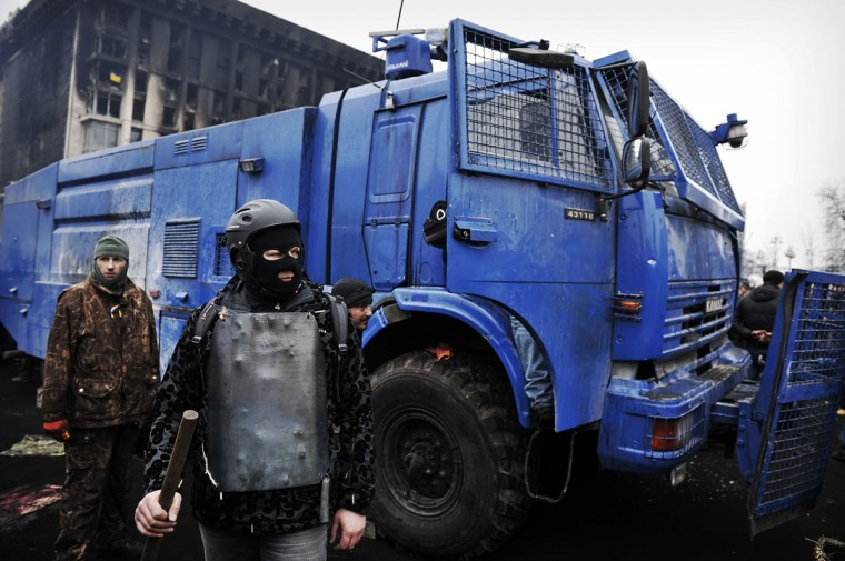 Anti-government protesters stand guard next to a police water cannon on the Independence square in Kiev on February 22, 2014. (Louisa Gouliamaki/AFP/Getty Images)