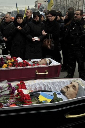 People pay their respects to two anti-government protesters killed during the recent clashes during a funeral service on the Independence square in Kiev on February 22, 2014. (Louisa Gouliamaki/AFP/Getty Images)