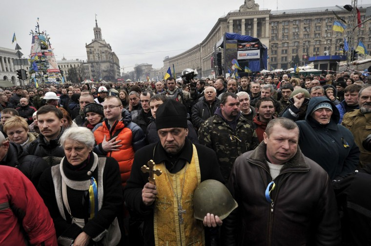 People attend a funeral service for two anti-government protesters killed during the recent clashes on the Independence square in Kiev on February 22, 2014. (Louisa Gouliamaki/AFP/Getty Images)