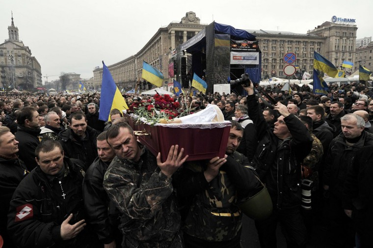 People carry a coffin during a funeral service for two anti-government protesters killed during the recent clashes on the Independence square in Kiev on February 22, 2014. A member of Ukraine's parliament said on February 22 that President Viktor Yanukovych has promised to submit his resignation in response to violence that left nearly 100 dead in anti-government unrest. (Louisa Gouliamaki/AFP/Getty Images)