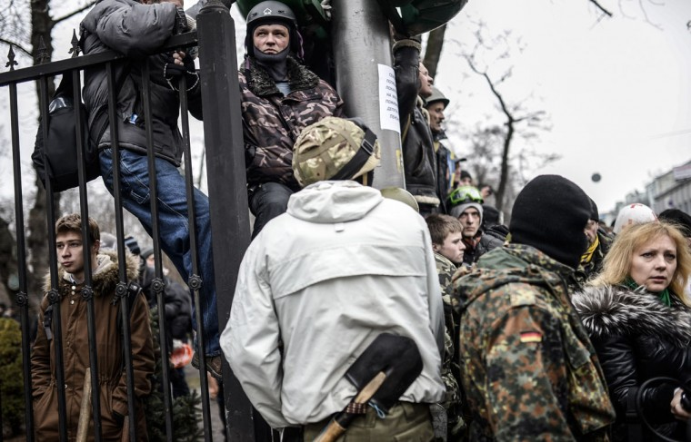 Anti-government protesters wait outside the parliament building in Kiev on February 22, 2014. Ukraine's parliament on February 22 voted to hold early presidential elections on May 25, passing a resolution stating that Viktor Yanukovych had failed to properly fulfil his duties as president. (Bulent Kilic/AFP Getty Images)