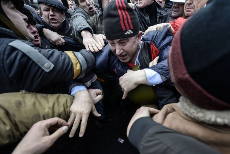 People beat an alleged member of parliament (center) in Kiev on February 22, 2014. Ukraine's parliament on February 22 voted to hold early presidential elections on May 25, passing a resolution stating that Viktor Yanukovych had failed to properly fulfil his duties as president. (Bulent Kilic/AFP Getty Images)