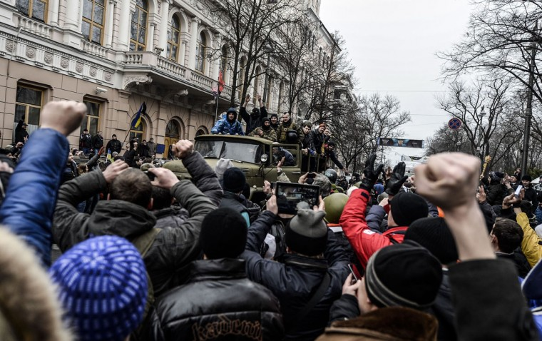People cheer in front of the parliament building in Kiev on February 22, 2014. Ukraine's parliament on February 22 voted to hold early presidential elections on May 25, passing a resolution stating that Viktor Yanukovych had failed to properly fulfil his duties as president. (Bulent Kilic/AFP Getty Images)