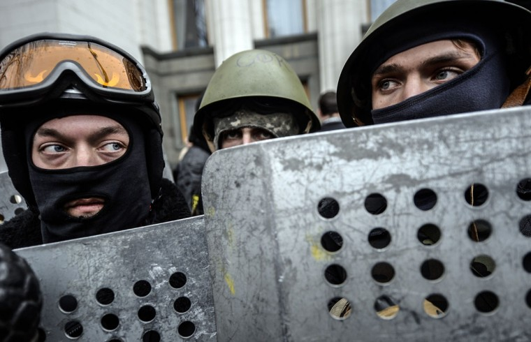 Anti-government protesters stand guard in front of the parliament building in Kiev on February 22, 2014. Ukraine's parliament on February 22 voted to hold early presidential elections on May 25, passing a resolution stating that Viktor Yanukovych had failed to properly fulfil his duties as president. (Bulent Kilic/AFP Getty Images)