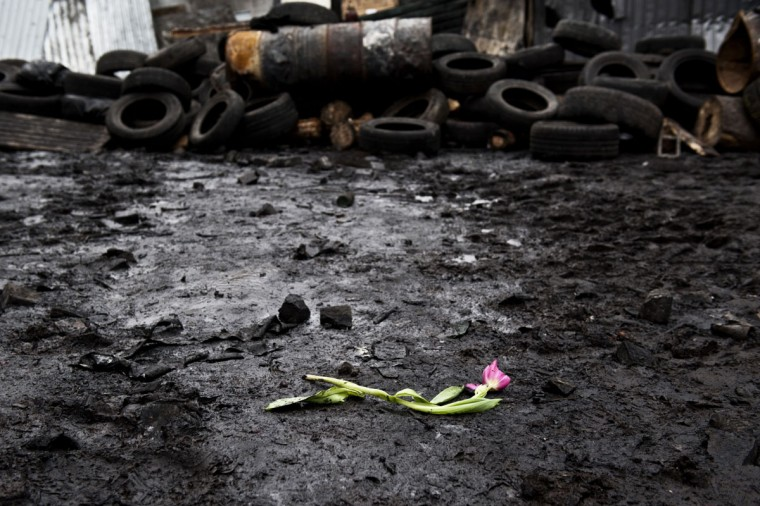 A flower is left on the burned floor next to a dismantled barricade in rememberance of the people killed during the clashes between anti-government activists and the Ukrainian police forces, in Kiev, on February 22, 2014, after a week of escalting violence. (Piero Quarant/AFP Getty Images)