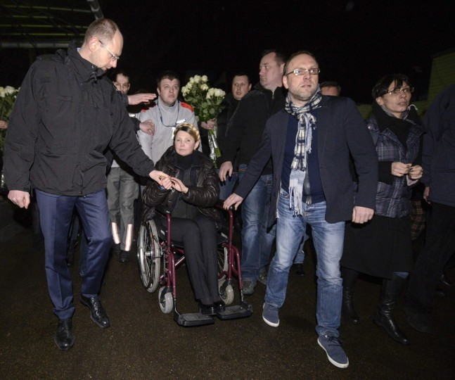 Ukrainian opposition leader Yulia Tymoshenko (center) holds her associate Arseny Yatsenyuk's hand (left) as she is transported on a wheelchair upon her arrival at the airport in Kiev February 22, 2014. (Andrew Kravchenko/Reuters)