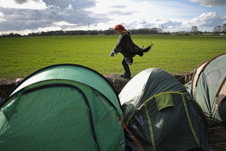 Court hearing on British frack protests: An anti-fracking campaigner walks along straw bales past tents near the Igas Barton Moss exploration facility on February 24, 2014 in Barton, England. Plans to evict activists, who have been camped outside the Barton Moss gas fracking exploration facility, have been put on hold while their lawyers make a legal challenge in the courts. Up to 60 campaigners have been on the site in Barton Moss Road since November last year and are waiting anxiously for the next court hearing on March 6, 2014. (Photo by Christopher Furlong/Getty Images)