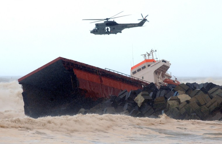 A helicopter flies over a Spanish cargo ship ''Luno'' which slammed into a dyke and split in two, injuring at least one sailor and raising concerns of a fuel leak, in Anglet, near the French port of Bayonne. The prefecture for the Pyrenees-Atlantiques region said efforts were underway to recover the sailors by helicopter but the rescue operation was being hampered by winds of up to 110 kilometres per hour (70 miles per hour). Officials said a fuel leak had been detected and an emergency plan known as Polmar had been activated to deal with maritime pollution. (Gaizka Iroz/Getty Images)