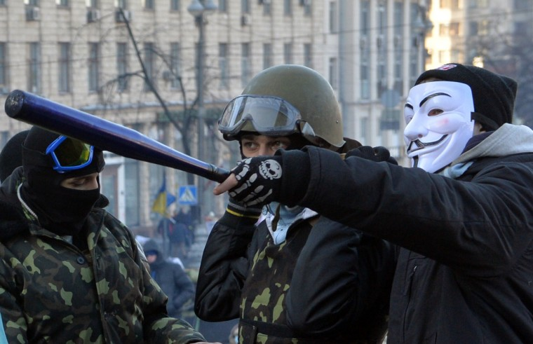 Anti-government protesters, one of them wearing a Guy Fawks mask, guard a barricade in Kiev. Ukraine's parliament will try again on February 5 to agree on curbing the presidency's powers, while the EU's foreign policy chief meets embattled President Viktor Yanukovych to press for a resolution of the political crisis. The crisis has sparked tensions between the West, which is considering sanctions against Ukrainian officials, and Russia, which has accused the EU and US of interference in the former Soviet republic. (Sergei Supinsky/Getty Images)