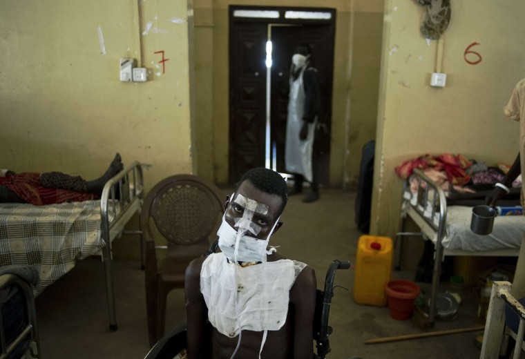 A patient being treated for multiple gunshot wounds to the face, chest and throat sits in a wheelchair in the Malakal teaching hospital. Recent fighting in the country has seen waves of brutal revenge attacks, as fighters and ethnic militia use the violence to loot and settle old scores, with the United Nations and rights workers reporting that horrific atrocities have been committed by both sides. Many fear the conflict has slid out of the control of political leaders, with ethnic violence and revenge attacks between the Dinka people of Kiir and the Nuer of Machar, the country's two largest groups. (Carl De Souza/Getty Images)