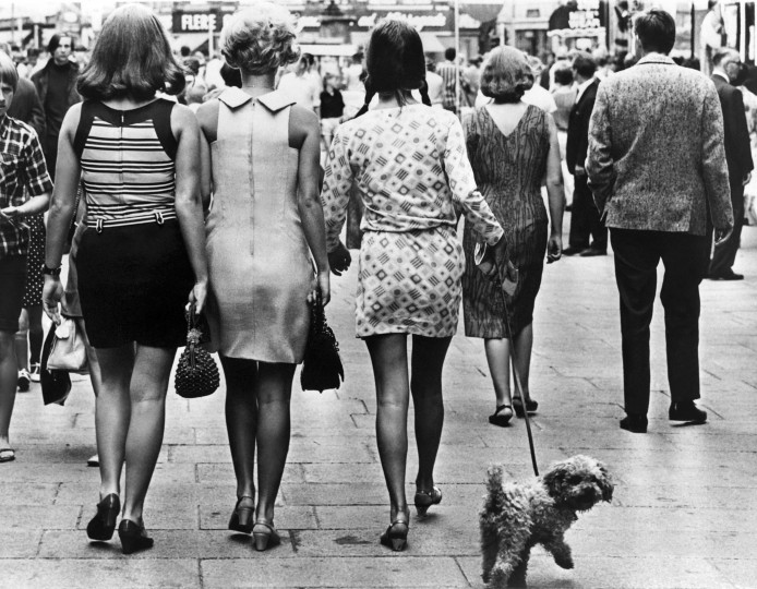 Young women wearing mini-skirts walk down a street with a poodle in Copenhagen on August 15, 1968.  The creator of the mini-skirt, British designer Mary Quant, turns 80 on February 11, still brimming with enthusiasm for fashion and women's rights. || AFP/Getty Images