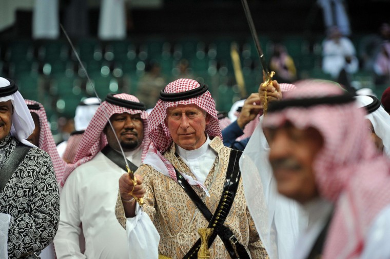 Britain's Prince Charles (C) wearing traditional Saudi uniform, dances with sword during the traditional Saudi dancing best known as 'Arda' performed during Janadriya culture festival at Der'iya in Riyadh. Charles arrived in Saudi Arabia on a private visit. (Fayez Nureldine/Getty Images)