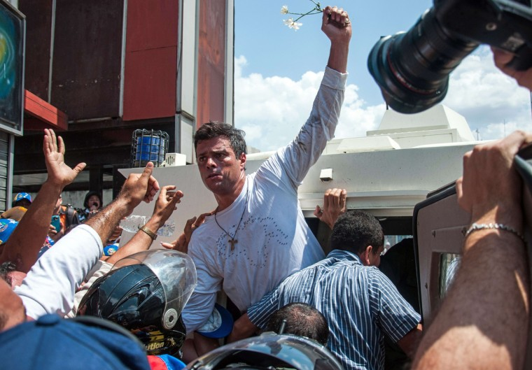 Leopoldo Lopez (C), an ardent opponent of Venezuela's socialist government facing an arrest warrant after President Nicolas Maduro ordered his arrest on charges of homicide and inciting violence, is escorted by the national guard into a vehicle after he turned himself in, during a demonstration in Caracas. Fugitive Venezuelan opposition leader Lopez, blamed by Maduro for violent clashes that left three people dead last week, appeared at an anti-government rally in eastern Caracas and quickly surrendered to the National Guard after delivering a brief speech. (Christian Hernandez/Getty Images)