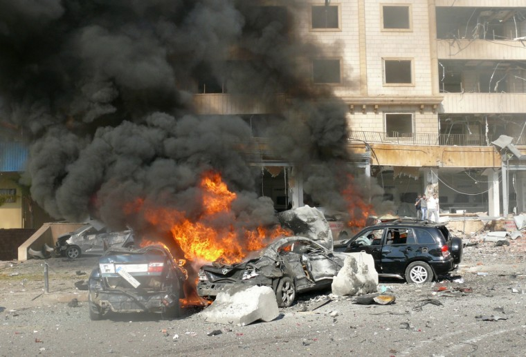 Flames rise from the wreckage of cars following a bomb explosion in a outhern suburb of the capital Beirut . Twin bomb blasts appeared to target the Iranian cultural centre, and an AFP photographer at the scene said the blasts had occurred beyond a security checkpoint at the centre, close to the building. (Getty Images)