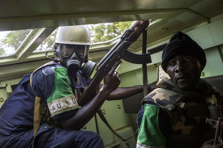 Republic of Congo policemen shoot at anti-Balaka forces at a road block in Bangui's Combatant neighborhood, Central African Republic. Heavy gunfire and explosions from rockets and grenades erupted on February 19 at the airport in the Central African Republic's capital Bangui where protesters have erected barricades against international forces based there, an AFP correspondent said. Bullets whistled past French soldiers guarding the main entrance to the airport, the correspondent said. (Fred Dufour/Getty Images)