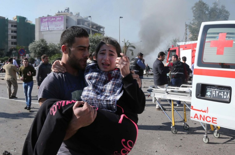 A Lebanese man carries an injured girl following a bomb explosion in a southern suburb of the capital Beirut. Twin bomb blasts appeared to target the Iranian cultural centre, and an AFP photographer at the scene said the blasts had occurred beyond a security checkpoint at the centre, close to the building. (Getty Images)