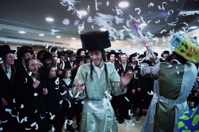 Jewish ultra-orthodox groom Aharon Krois celebrates his wedding with Rivka Hannah (Hofman) (unseen) during the Mitzvah Tans dance ritual following her wedding in an ultra-orthodox neighborhood of Jerusalem. During the Mitzvah Tans dance ritual the bride will dance with members of the community, family and with her groom at the end of the wedding ceremony. (Menahem Kahana/Getty Images)