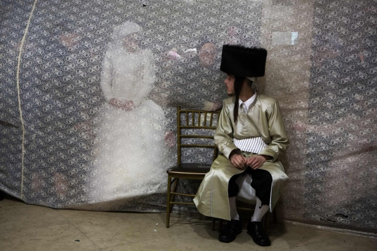 Jewish bride Rivka Hannah (Hofman) looks at her groom Aharon Krois from behind a curtain during the Mitzvah Tans dance ritual following their wedding in an ultra-orthodox neighborhood of Jerusalem. During the Mitzvah Tans dance ritual the bride will dance with members of the community, family and with her groom at the end of the wedding ceremony. (Menahem Kahana/Getty Images)
