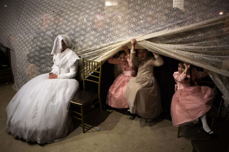 Children peep from behind a curtain next to Jewish ultra-orthodox bride Rivka Hannah (Hofman) during the Mitzvah Tans dance ritual following her wedding in an ultra-orthodox neighborhood of Jerusalem. During the Mitzvah Tans dance ritual the bride will dance with members of the community, family and with her groom at the end of the wedding ceremony. (Menahem Kahana/Getty Images)