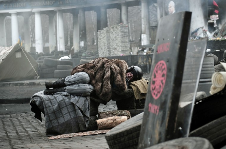 A man sleeps at a barricade near the Dynamo Kiev stadium in Kiev. Ukraine put police and interior ministry troops on alert February 27 after armed men seized the government and parliament in the pro-Russian region of Crimea, interior minister Arsen Avakov said. (Louisa Gouliamaki/Getty Images)