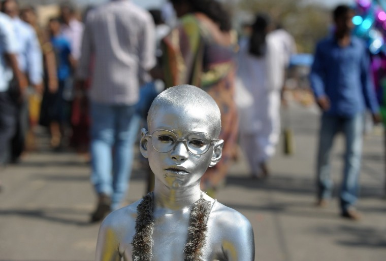 An Indian boy dressed as Mahatma Gandhi begs for alms from Hindu devotees during the Maha Shivaratri festival outside the Keesaragutta Temple on the outskirts of Hyderabad. The festival of Maha Shivaratri is marked by Hindus by fasting and offering prayers in a night long vigil. (Noah Seelam/Getty Images)
