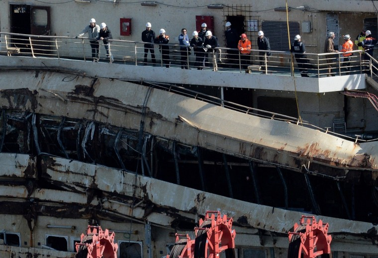 The captain of the wrecked Costa Concordia cruise ship Francesco Schettino (C-without helmet) stands on the wrecked Costa Concordia cruise ship in Giglio Port . Schettino returned to the site of the disaster for the first time as part of the trial against him. (Filippo Monteforte/Getty Images)