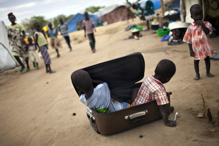 Children play with a suitcase in a IDP camp for the Nuer ethnic group inside the UNMISS compound in Bor, South Sudan. War crimes have been committed by all sides in conflict-wracked South Sudan, Human Rights Watch said Thursday, reporting widespread atrocities in weeks of carnage in the world's youngest nation. Thousands have been killed and almost 900,000 forced from their homes by over two months of battles between rebel and government forces, backed by troops from neighbouring Uganda. (Jim Lopez/Getty Images)