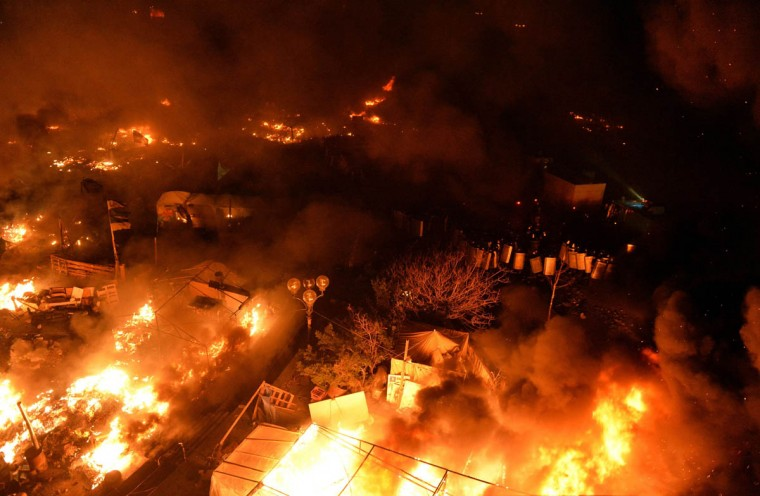 Anti-government protesters clash with the police during their storming of Independence Square in Kiev on February 18, 2014. Flames engulfed the main protest camp in Kiev late Tuesday as police stormed it during the deadliest day of violence in three months of demonstrations, in which at least 11 people were killed and alarm rippled across Europe and beyond. (Sergei Supinsky/Getty Images)