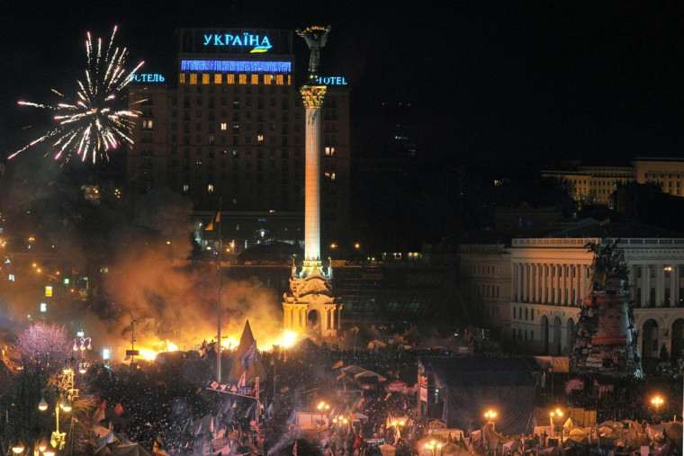 Anti-government protesters clash with the police during their storming of Independence Square in Kiev on February 18, 2014. Flames engulfed the main anti-government protest camp on Independence Square on Tuesday as riot police tried to force demonstrators out following the bloodiest clashes in three months of protests. The iconic square turned into a war zone as riot police moved slowly through opposition barricades from several directions, hurling stun grenades and using water cannon to clear protestors. (Genya Savilov/Getty Images)