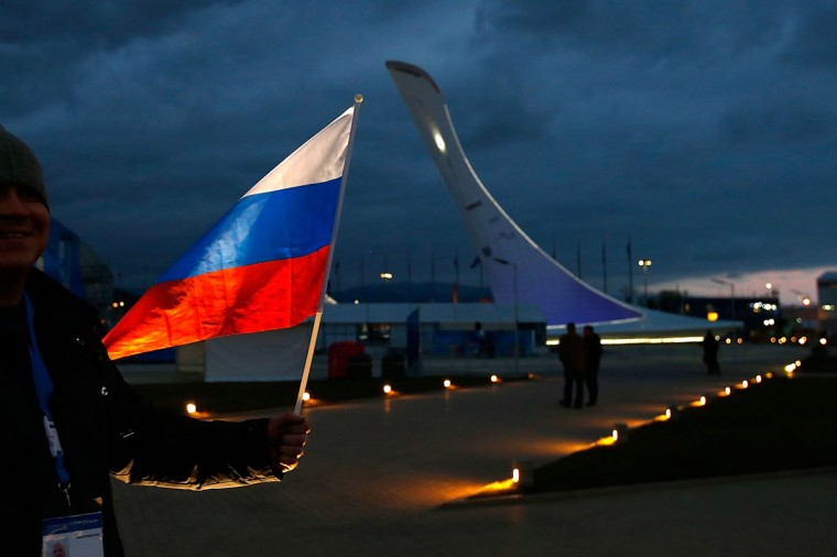 A fan holds a Russian Flag in front of the Olympic Cauldron ahead of the Sochi 2014 Winter Olympics at the Olympic Park. (Photo by Joe Scarnici/Getty Images)