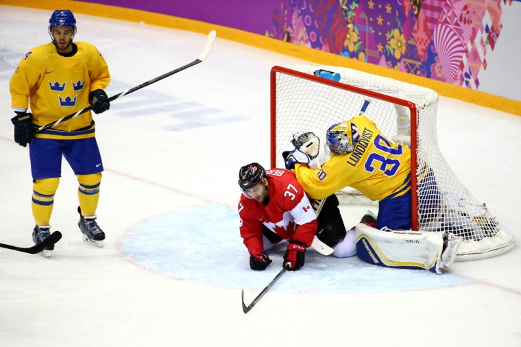 Patrice Bergeron of Canada slides into the net of Henrik Lundqvist of Sweden. (Photo by Streeter Lecka/Getty Images)
