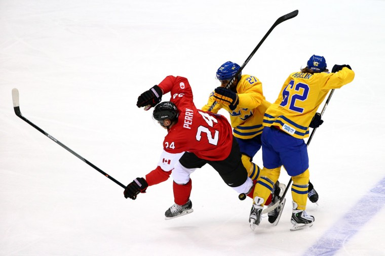 Corey Perry of Canada skates against Johnny Oduya and Carl Hagelin of Sweden during the gold medal match. (Photo by Clive Mason/Getty Images)