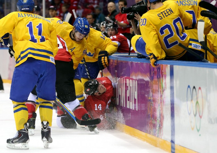 Chris Kunitz of Canada crashes into the boards against Gabriel Landeskog and Patrik Berglund of Sweden during. (Photo by Bruce Bennett/Getty Images)