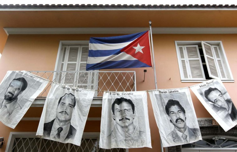 """Posters with portraits of five Cubans jailed in the United States - Rene Gonzalez Sehwerert, Gerardo Hernandez Nordelo, Fernando Gonzalez Llort(C), Ramon Labanino Salazar and Antonio Guerrero Rodriguez - are dispayed in this April 7, 2010 file photo in front of Cuba's Consulate in Sao Pablo, Brazil. One of the so-called """"Cuban Five"""" -- intelligence agents convicted in a 2001 US spy case that made them heroes in Havana -has been told he will be released from prison, his lawyer told a Miami newspaper on January 29, 2014. Fernando Gonzalez, who is serving a 17-year prison sentence for not registering as a foreign agent and possessing false identity papers, would be the second member of the group to be released. His lawyer Ira Kurzban told El Nuevo Herald newspaper that the Bureau of Federal Prisons had set Fernandez's release for February 27 for good conduct. Fernandez was arrested in 1998 along with four other Cuban intelligence agents for infiltrating the Key West Naval Air Station and Cuban exile groups in Miami. 