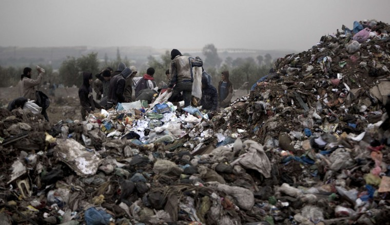 Palestinian workers collect rubbish from a garbage dump in search of recyclable material on February 2, 2014 in Gaza City. (Mahmud Hams/AFP/Getty Images)